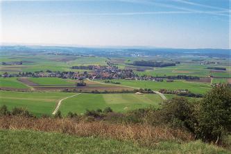 Von erhöhtem Standpunkt aus blickt man auf eine leicht wellige Stufenlandschaft mit Grün- und Ackerflächen. Im Mittelgrund ist eine Ortschaft erkennbar. Am Horizont reihen sich mehrere bewaldete Höhenzüge aneinander.