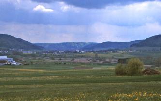 Das Bild zeigt eine streifige, nach rechts hin ansteigende Grün- und Ackerlandschaft mit Schilfflächen im Mittelgrund. Links und rechts sowie mittig erheben sich bewaldete Hänge.