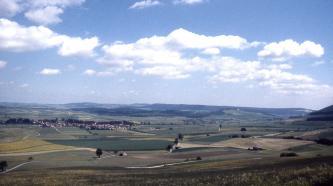 Das Bild zeigt ein buntes Mosaik aus gelben, grünen und braunen Ackerflächen, das sich bis zum Horizont fortsetzt. Links im Mittelgrund ist eine Siedlung zu erkennen, dahinter erheben sich flache bewaldete Höhenzüge bis zum rechten Bildrand.