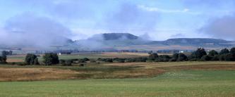 Das Bild zeigt eine grüne Ebene, an die sich eine braun-grüne Senke anschließt. Dahinter zeigt sich ein Streifen von Gebüsch und Bäumen, ehe eine wieder ansteigende Ackerlandschaft folgt. Nebelschwaden verhüllen im Hintergrund aufragende Höhenzüge.