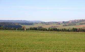 Blick über eine hochgelegene Wiese und Baumspitzen auf im Hintergrund liegende, hügelige Äcker und Felder. Links sind mehrere Waldzungen zu sehen, rechts liegt eine Siedlung auf der Hügelkuppe.