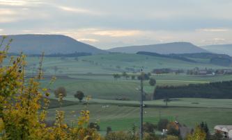 Das Bild zeigt eine vorwiegend grüne, hügelige Ebene mit Waldzungen rechts vorne sowie im Hintergrund. Ebenfalls im Hintergrund erheben sich links und rechts bewaldete Höhenzüge. In der Mitte dazwischen sind höhere Berge erkennbar.