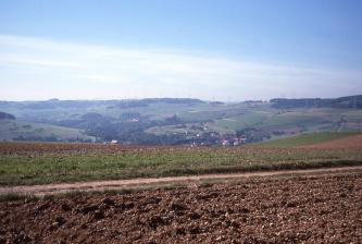Das Bild zeigt mehrere im Vordergrund liegende Äcker sowie im Hintergrund ein tiefes, welliges Tal mit Acker-, Grün- und Waldflächen.