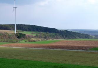 Das Bild zeigt mehrere Streifen unterschiedlicher, flach bis leicht gewellter Ackerflächen. Von links nach rechts steigt daran angrenzend ein teilweise bewaldeter Hang auf. Rechts steht zudem ein Windkraftrad.