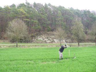 An eine ebene Grünfläche schließt sich im Hintergrund ein in der Mitte felsiger, rundum von Kiefern bestanderer Hang an. Im Vordergrund schwingt ein Bodenkundler einen Bohrhammer.