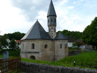 Das Bild zeigt eine scheinbar halb im Boden versunkene Kapelle aus graubraunem Stein mit einem schmalen Turm in der Mitte. Vorne und rechts hinten sind dunkle, einen Erdhügel umfassende Mauerstücke erkennbar.