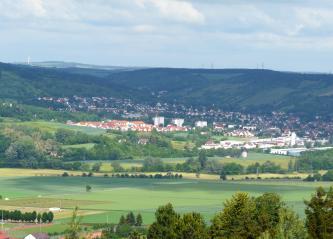 Blick auf ein im Vordergrund flaches, ackerbaulich genutztes Tal und ansteigendes Gelände sowie eine Siedlung im Hintergrund. Teilweise bewaldete Hänge begrenzen die Ortschaft.