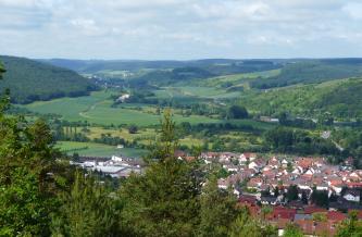 Von erhöhtem Standort aus blickt man auf eine Siedlung im Vordergrund sowie ein sich anschließendes grünes Tal mit bewaldeten Höhen im Hintergrund.