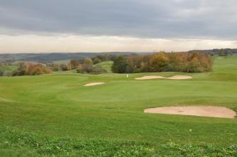Das Bild zeigt einen hügeligen, grünen Golfplatz. Auch einzelne Sandinseln und Baumgruppen sind zu sehen.