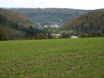 Blick über einen hochgelegen, begrünten Acker auf ein von bewaldeten Hügeln umschlossenes, besiedeltes Tal.