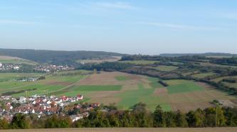 Das Bild zeigt einen weiten, nach links hin abgeflachten Hang mit einem bunten Mosaik aus Siedlungen links, Waldstreifen und Ackerflächen. Rechts, auf der Kuppe des Hanges, sind auch Hecken und schmale Steinhügel erkennbar.