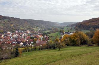 Blick auf ein links besiedeltes Tal mit zwei zu den Seiten hin aufsteigenden, größtenteils bewaldeten Hängen. Im Vordergrund, zum Betrachter hin, erstrecken sich Gehölzstreifen und Grünflächen.