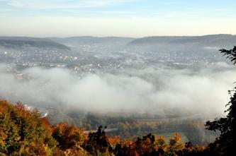 Aus großer Höhe blickt man auf eine von bewaldeten Höhen umschlossene, stark besiedelte Landschaft. Dichte Wolkenschwaden verdecken allerdings einen Teil dieser Landschaft.