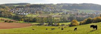 Das Bild zeigt eine weite, ovale flache Landschaft mit dichter Besiedlung, die von teilweise bewaldeten Hügeln umschlossen wird. Im Vordergrund, zum Betrachter aufsteigend, sind links braune Ackerflächen sowie rechts eine Pferdeweide zu sehen.