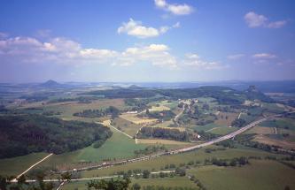 Blick aus großer Höhe auf eine hügelige Landschaft mit Wald- und Ackerflächen. Drei Bergkuppen stechen aus der Landschaft hervor.