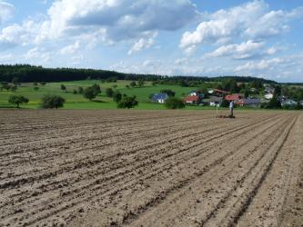 Das Bild zeigt einen graubraunen, gefurchten Acker. Im Hintergrund links sind grüne Hügel und Waldstreifen, rechts eine Siedlung zu erkennen.
