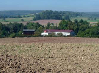 Blick über hochliegende graubraune Äcker auf im Hintergrund verteilte, rötlich braune Ackerflächen. Dazwischen und dahinter liegen Waldstreifen.