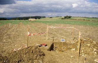 Auf einem teilweise begrünten Stoppelacker wurde ein Bodenprofil aufgegraben. Die flache, unterhalb des Pflughorizonts steinige Grube sowie das aufgehäufte, mit Steinen vermischte Bodenmaterial ist gelbbraun gefärbt.