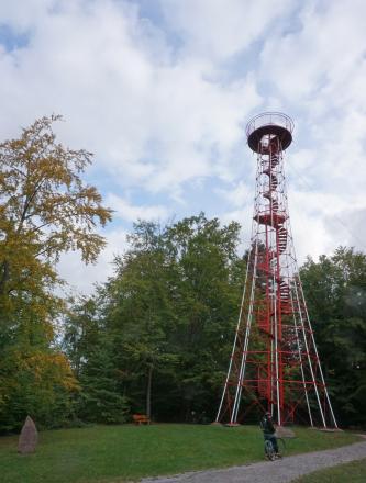 Blick auf einen kegelförmigen, aus dünnen Stahlrohren erbauten Aussichtsturm. Die obere Aussichtsplattform ist durch eine immer enger verlaufende Wendeltreppe erreichbar. Der Turm steht auf flachem Grün, dahinter sind Bäume.