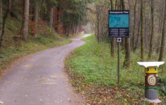 """Blick auf einen geteerten, kurvigen Weg, der in einen herbstlichen Wald führt. Rechts steht ein Hinweisschild mit der Überschrift """"Geologischer Pfad""""; weiter vorn zeigt sich eine bemalte Figur."""