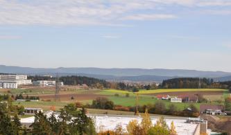 Von erhöhtem Standort aus blickt man auf eine flachhügelige Landschaft mit Wiesen, Äckern und Wald. Auch einzelne Höfe rechts und Neubauten links sind zu sehen. Weiter hinten ist in einer Senke eine Stadt sichtbar. Am Horizont ragen bewaldete Berge auf.