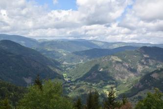 Blick aus großer Höhe über mehrere, bis zum Horizont aneiandergereihte bewaldete Bergrücken. Zwischen den Bergen sind schmale Täler eingeschnitten.