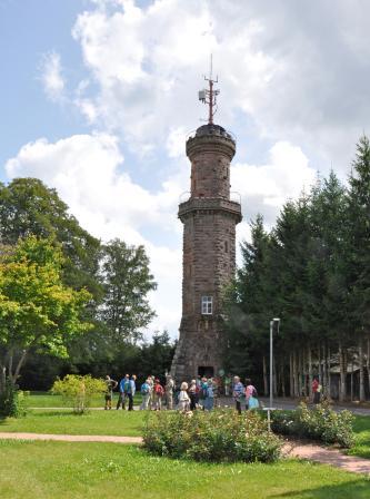 Das Foto zeigt einen grauen Steinturm, der in einem Parkgelände mit Wiesen, Bäumen und Blumenhecken steht. Der Turm hat zwei Aussichtsplattformen und ist unten achteckig, oben gerundet. Vor dem Eingang warten Besucher.