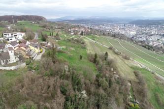 Blick aus der Luft auf einen Hügel, welcher neben Feldern teilweise mit Wald bedeckt ist. Auf der Spitze des Hügels befindet sich eine kleine Siedlung. Rechts im Hintergrund ist eine größere Siedlung und eine Bergkette zu erkennen.