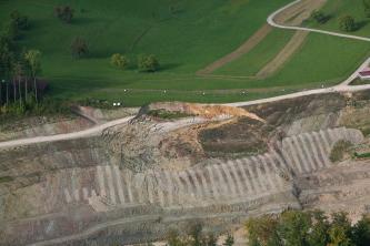 Blick aus großer Höhe auf eine Hangrutschung. Dabei wurde ein Teilstück einer im Bau befindlichen Straße weggerissen.