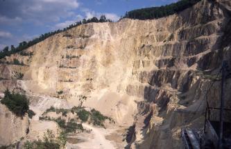 Blick auf eine schön gestufte, nach rechts ansteigende Steinbruchwand. Die Farbe des Gesteins wechselt von gelblichem Braun links zu rötlichem Braun rechts.