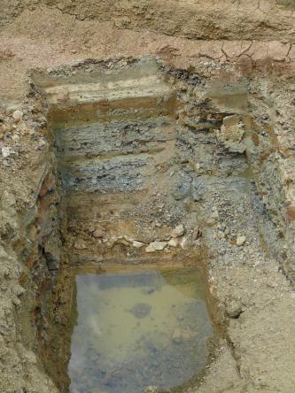 Blick von oben in eine kleine, rechteckige Grube, auf dessen Boden Wasser steht. Es steht hellgelbes mit mittelbraunes Gestein an.