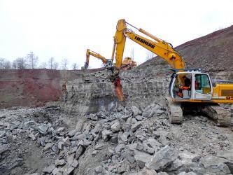 Gezeigt werden mehrere Bagger, die in einem Steinbruch Gestein abbauen. Im Vordergrund wird eine niedrige Wand weiter zerkleinert, loses Gestein und Schutt liegt verstreut davor.
