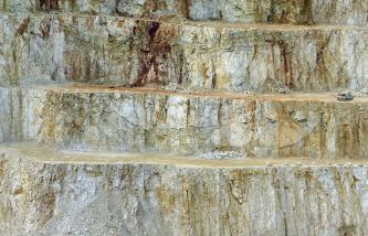 Blick auf eine abgestufte Steinbruchwand mit drei waagrecht verlaufenden Fahrstraßen und teilweise angehäuften Schutthalden. Das Gestein ist mehrfarbig, von hellgrau bis braun.