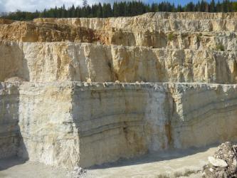 Blick auf mehrere, terrassenförmig aufeinander folgende Steinbruchwände. Die Farbe des Gesteins wechselt von weißlichen Tönen vorne bis zu Braun oben links.