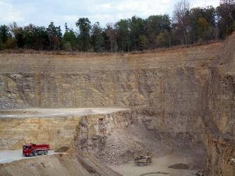 Blick in einen Steinbruch. Im Hintergrund eine hohe bräunlich graue Gesteinswand, die rechts nach vorne abknickt. Im Mittelgrund links ist eine halbhohe Sohle vorgelagert. Davor liegen Abraumhalden und stehen Fahrzeuge.