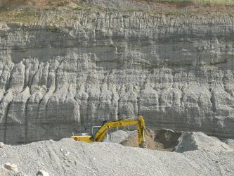 Blick auf eine bildfüllende Steinbruchwand. Dem grau bis bräunlich gefärbten, zahnartig gefurchten Gestein ist eine Abraumhalde mit Bagger vorgelagert.