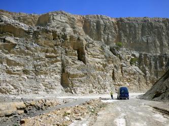 Blick in einen Steinbruch mit zwei sehr hohen, gebirgsähnlichen Wänden. Die vordere, bräunlich graue Gesteinswand steigt nach links hin an. Im Vordergrund links Gesteinsreste sowie rechts ein Fahrweg mit abgestelltem Fahrzeug.