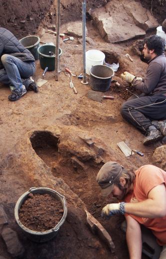 Das Foto zeigt längliche Vertiefungen in einem rötlich braunen Boden. Zwei halb liegende, halb knieende Männer rechts haben den Boden aufgegraben. Teils mit Erdmaterial gefüllte Eimer sowie verschiedene Werkezuge wie Maurerkellen stehen und liegen herum.
