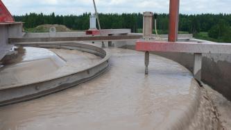 Ausschnitt einer Aufbereitungsanlage für Sand. In metallenen runden Becken wird das Bodenmaterial durch Wasser gereinigt.