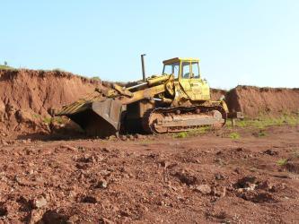 Das Bild zeigt den Abbau von dunkelrotem Gestein in einem Steinbruch. Der Abbau findet durch einen gelben Bagger in der Bildmitte statt.