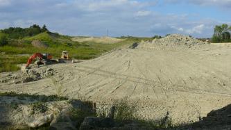 Blick von erhöhtem Standpunkt in eine Tongrube, in welcher das hellbeige Material mithilfe von Planierrraupe und Löffelbagger, zu sehen am linken Bildrand, abgebaut wird.