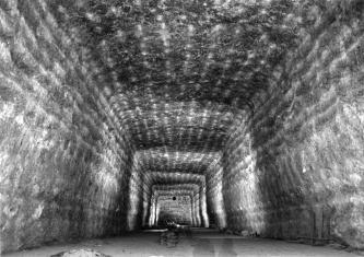 Blick in eine rechteckige Abbaukammer von Steinsalz, mit strahlenförmig vom hinteren Ende ausgehenden, schwarzen, grauen und weißen Linien.