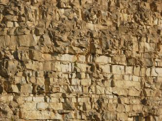 Teilansicht von rötlich braunem, in kleineren Blöcken auf- und nebeneinanderliegendem Gestein einer Steinbruchwand.