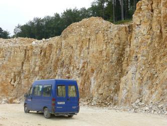 Blick von schräg rechts auf eine Abbauwand aus gelblich-beigem, eng-geklüftetem und gebanktem Gestein. Vor der Wand steht ein blauer Van.