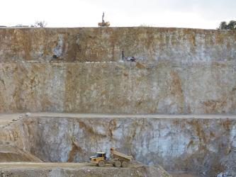 Das Bild zeigt eine dreistufige, sehr hohe Abbauwand in einem Steinbruch. Das anstehende Gestein ist beige mit bräunlichen und weißlichen Bereichen. Mittig vor der Wand steht ein Abbaufahrzeug.