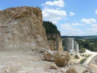 Blick von schräg oben in einen Steinbruch: Im Vordergrund links befindet sich eine Abbauwand aus hellgelbem Gestein, im Hintergrund rechts sind Industrieanlagen und dahinter Landschaft zu erkennen.