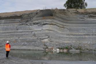Gezeigt wird die Abbauwand eines Steinbruches. Die dünnen, von hellgrau über dunkelgrau bis braun gefärbten Lagen machen rechts der Bildmitte einen wellenförmigen Knick. Ganz links steht ein Mensch mit Warnweste.