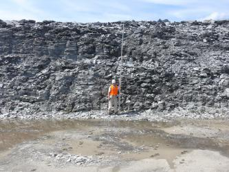 Das Bild zeigt die halbhohe Abbauwand eines Steinbruches. Das hellgraue Gestein ist plattig und scherbig. In der Bildmitte hält ein Arbeiter mit Schutzweste und Helm einen Maßstab hoch. Vor der Wand stehen Wasserlachen.