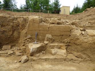 Das Bild zeigt eine eingezäunte Grube, in der braunes Gestein abgebaut wird. Einzelne glattgestrichene Blöcke stehen leicht hervor. Ein Hammer zeigt die Größe an.
