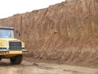 Blick von der Seite auf eine Abbauwand in einer Lehmgrube. Der anstehende Lehm ist mittelbraun. Links vor der Wand steht ein gelbes Fahrzeug.